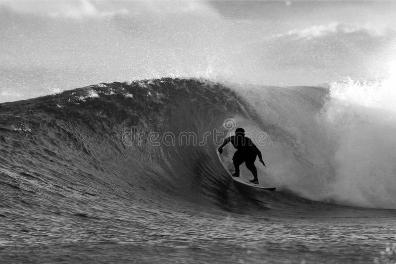 Surfer noir et blanc surfant le tube images libres de droits