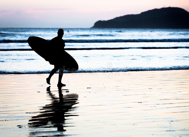 Surfer non identifié marchant sur le bord de la mer photographie stock
