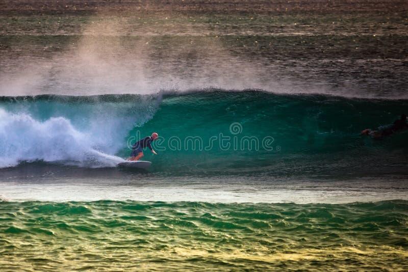 Surfer op Blauwe Oceaangolf in Bali stock foto