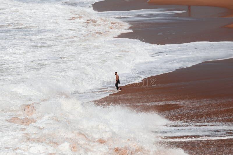 Surfer op de kust tussen verpletterende golven in Cadiz, Spanje royalty-vrije stock afbeelding