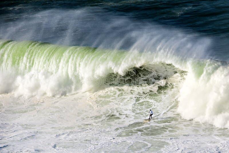 Surfer op Getxo uitdaging van reusachtige golven stock afbeeldingen
