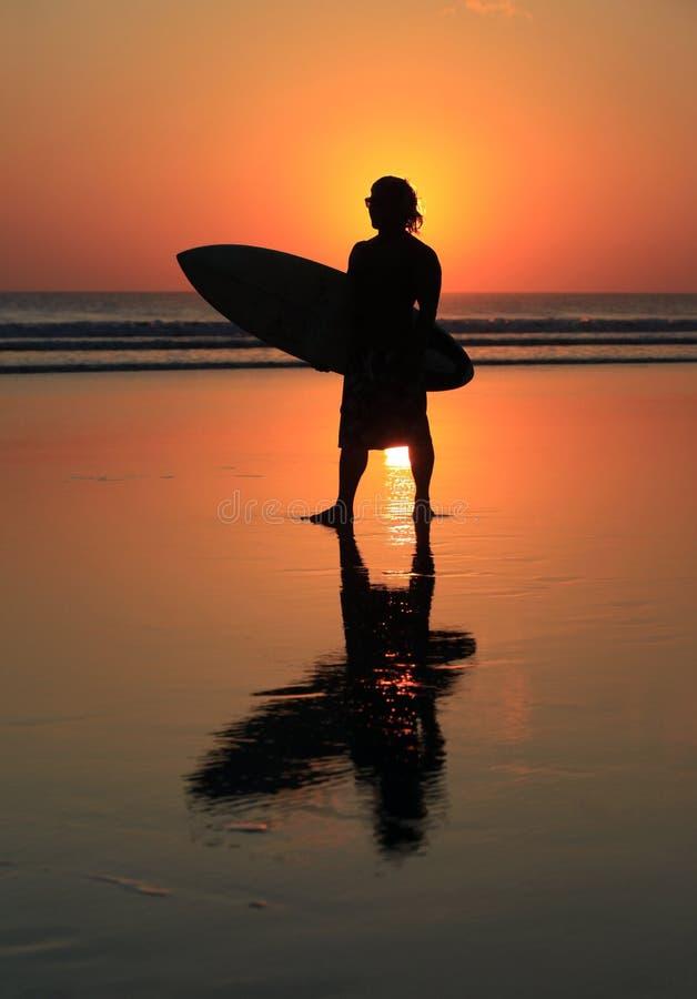 Surfer op zonsondergang royalty-vrije stock afbeeldingen