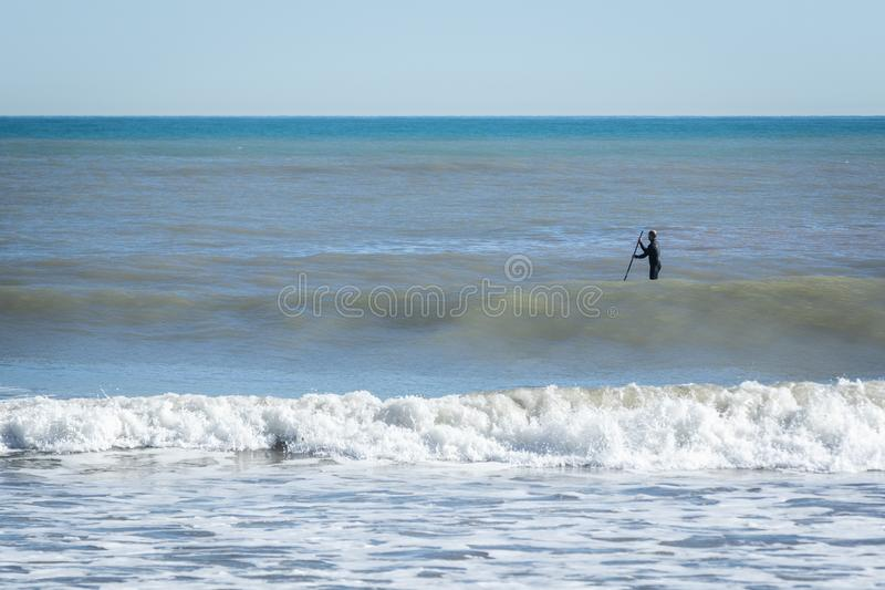 Surfer with paddle board catching the wave royalty free stock photos