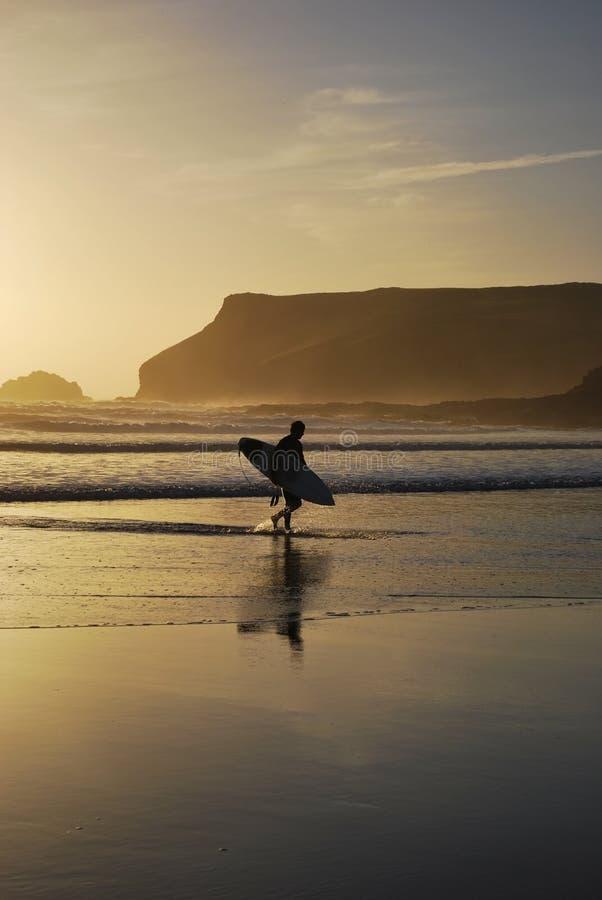 Surfer on Polzeath Beach, Cornwall, UK royalty free stock image