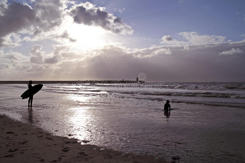 Surfer prêt à surfer au coucher du soleil image libre de droits