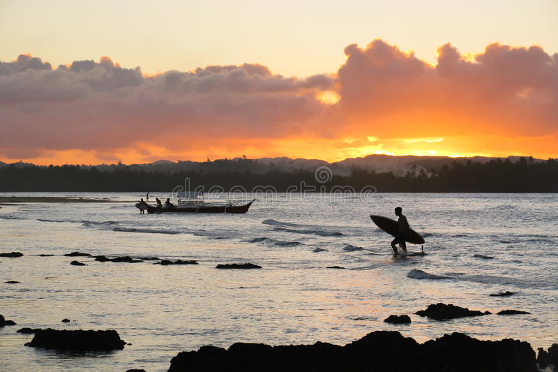 Surfer returning to the beach at sunset (silhouette) stock image