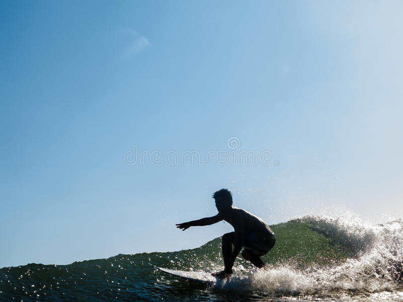 Surfer rides across wave stock photos