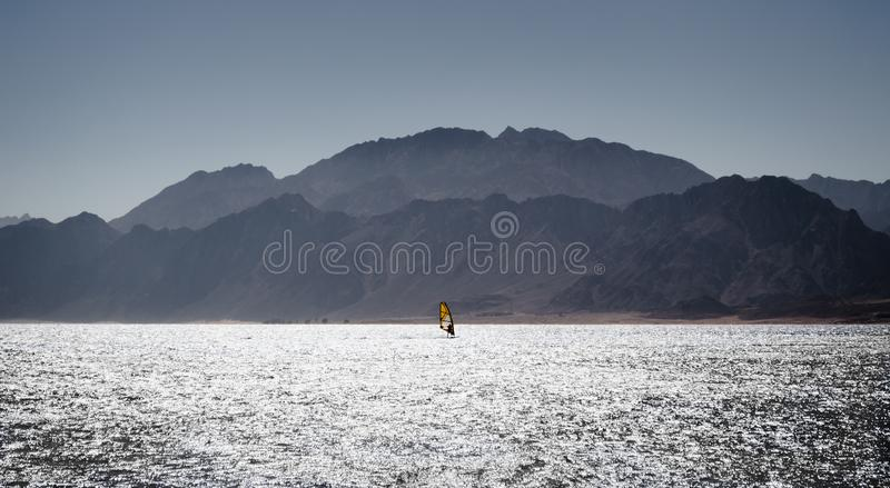 Surfer rides in the Red Sea against the backdrop of the coast with high rocky mountains in Egypt Dahab royalty free stock images
