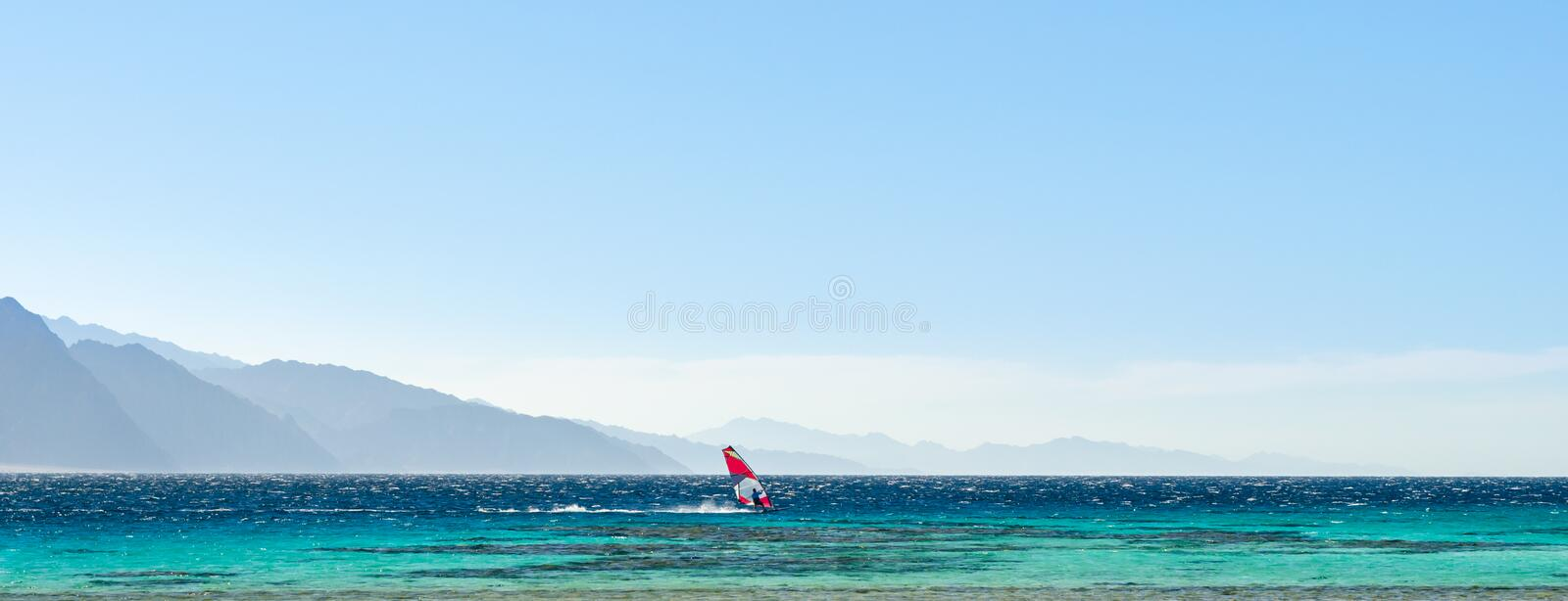 Surfer rides in the Red Sea against the backdrop of high rocky mountains and a blue sky with clouds in Egypt Dahab royalty free stock photos