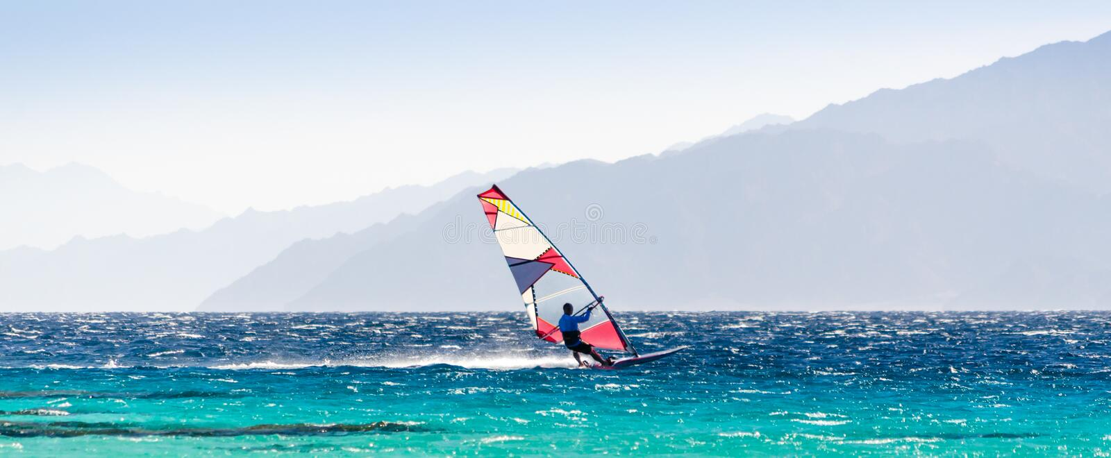 Surfer rides in the Red Sea on the background of the rocky coast in Egypt Dahab stock photo