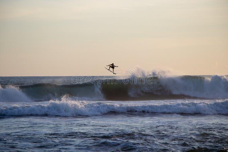 Surfer riding wave at Echo Beach Canggu Bali Indonesia stock photo