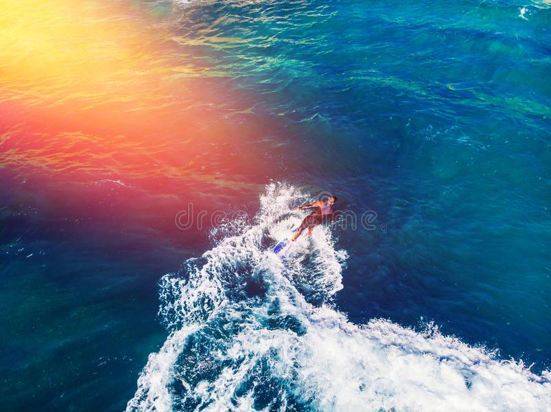Surfer rows up to catch crest of wave in blue ocean. Concept surfing. Top view royalty free stock photography