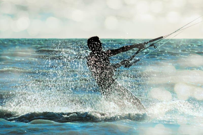 Surfer se précipitant par la mer dans un nuage de jet, plan rapproché image stock