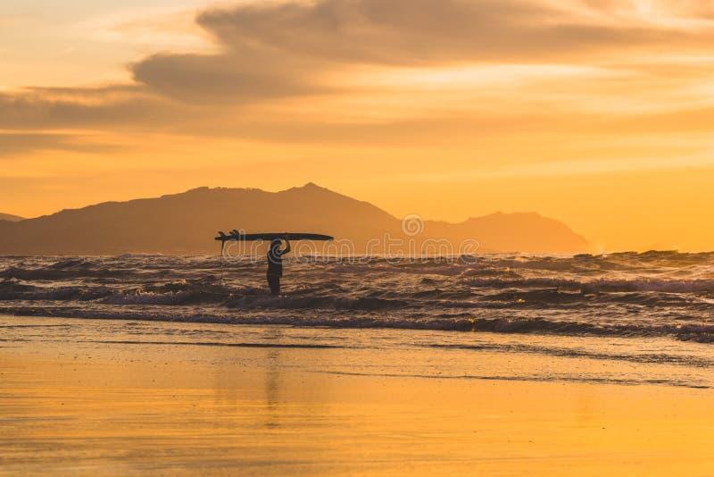 Surfer segurando o surfboard em sua cabeça Belo pôr do sol dramático no País Basco, norte de Espanha foto de stock