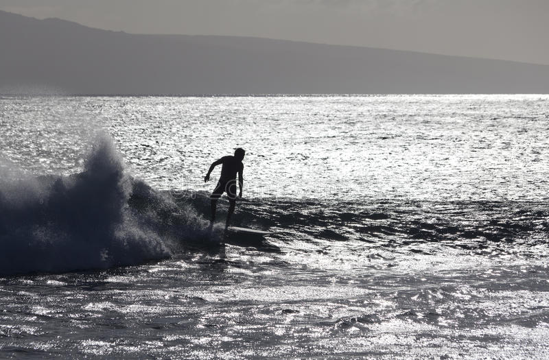 Surfer silhoutted against the silver waves stock photography