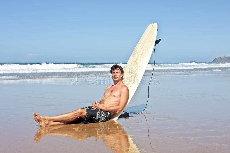 Surfer sitting against his surfboard stock photos