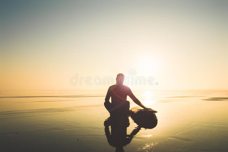 A surfer sitting by a surfboard on a misty afternoon looking out to sea. With deliberate sun flare. Saunton, Devon, UK stock images
