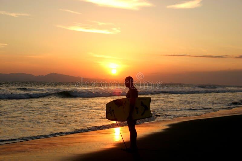 Surfer am Sonnenuntergang lizenzfreie stockbilder