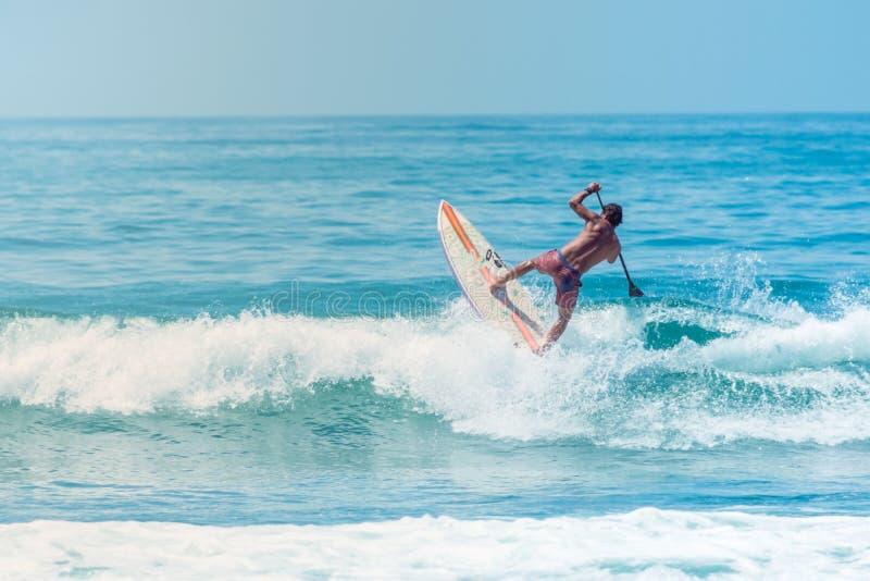 Surfer springende golf met een raad bij het Strand van Sayulita Nayarit royalty-vrije stock foto's