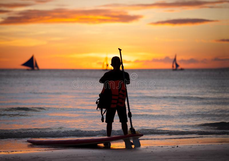 Surfer standing next surfboard. And looking at sunset sea stock photo