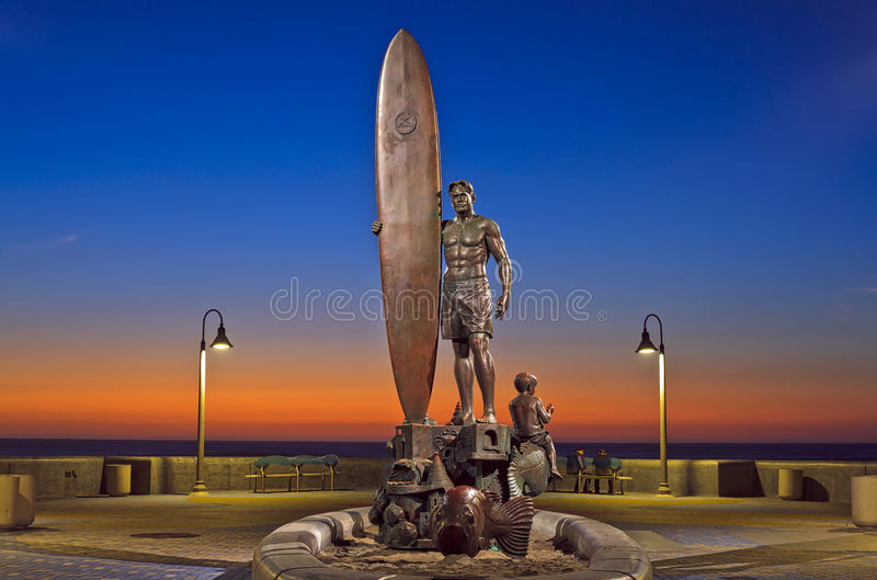 Surfer Statue with Colorful Sunset Sky in Southern California. Imperial Beach, California, USA - 29 October 2015: The Spirit of Imperial Beach bronze sculpture royalty free stock image