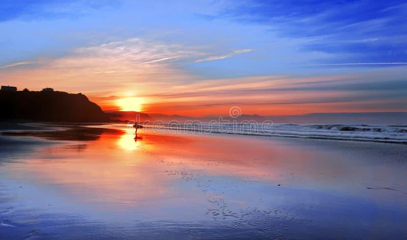 Surfer in strand bij zonsondergang met bezinningen stock afbeeldingen