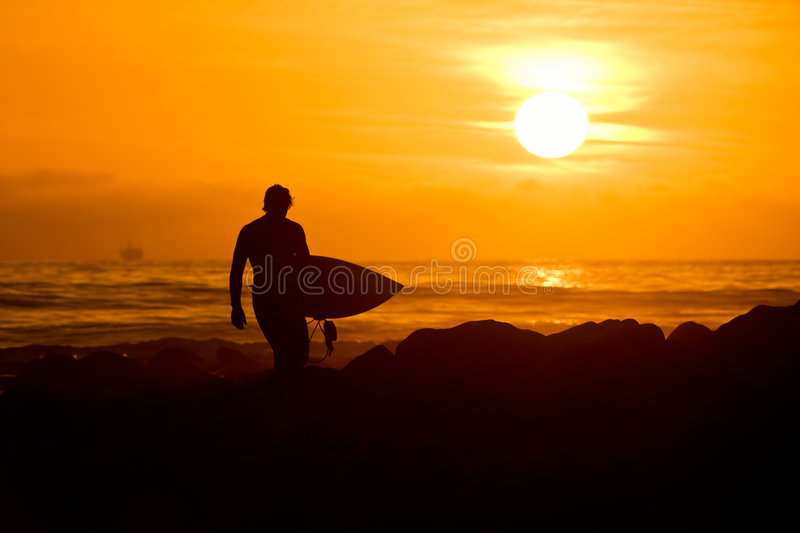 Surfer at Sunset. Surfer Walking on Beach at Sunset stock photos