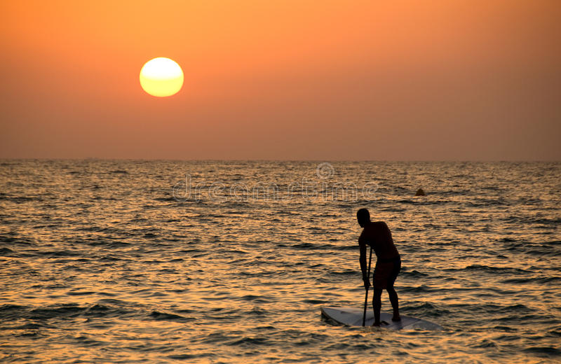 A surfer at sunset stock photography
