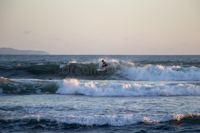 Surfer riding wave at Echo Beach Canggu Bali Indonesia stock photos