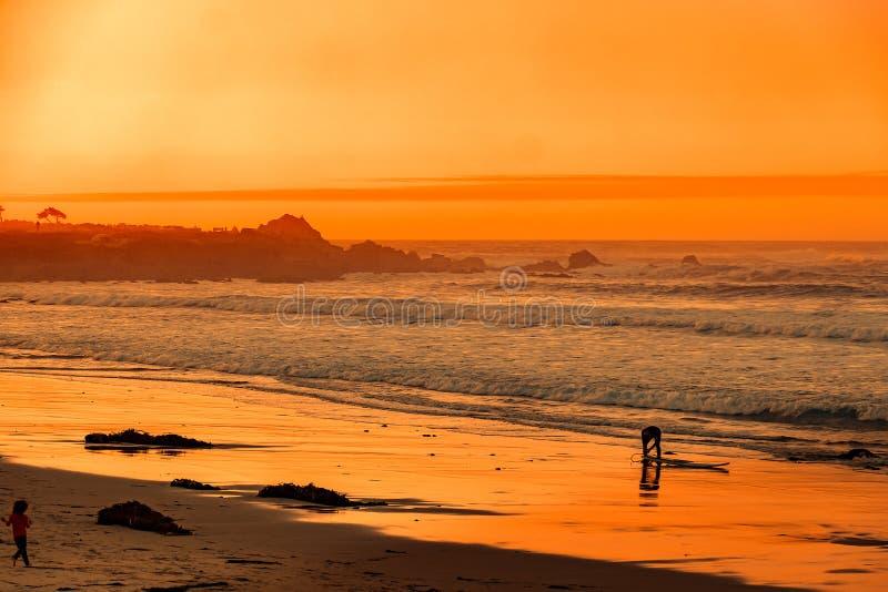 Surfer sur la plage à la Carmel-par-le-mer photographie stock