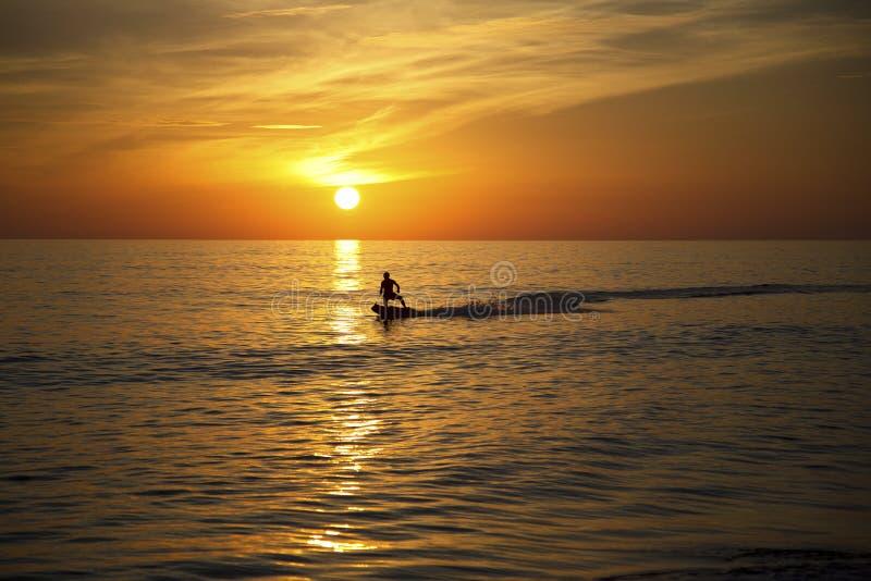 Surfer surfant au coucher du soleil photos stock