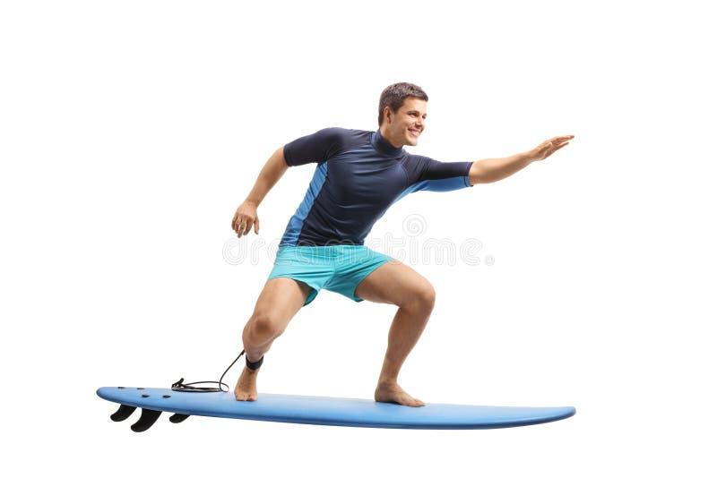 Surfer surfant sur une planche de surf image stock
