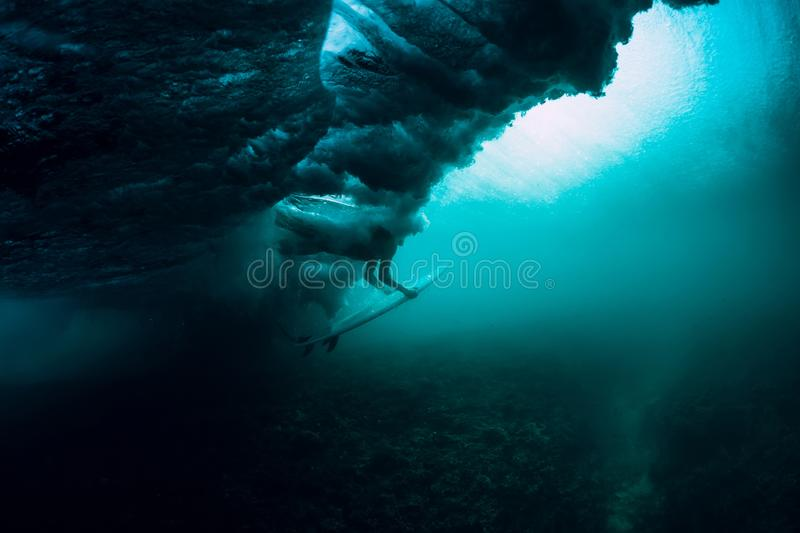 Surfer with surfboard dive underwater with under big wave. Surfer with surfboard dive underwater with under wave royalty free stock images