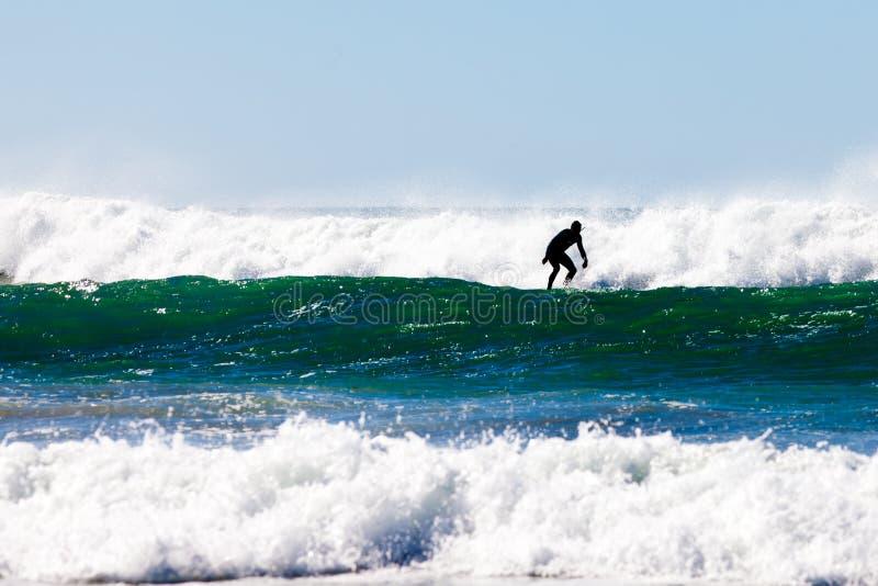 Surfer in surfenden brechenden Wellen des Wetsuit weg vom Strand lizenzfreies stockbild