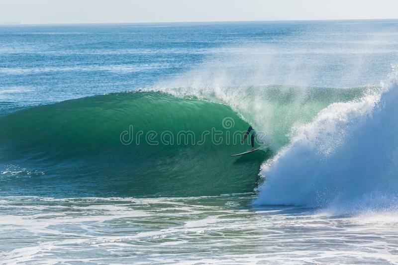 Surfer Surfing Hollow Wave Tube Ride. Surfer surfing inside hollow ocean wave for a tube ride closeup photo action royalty free stock image