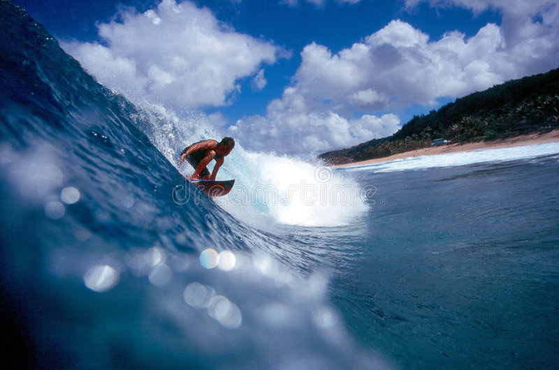 Surfer Surfing on the North Shore in Blue Hawaii. Stock Photo of a surfer riding a blue wave on the North Shore of Oahu, Hawaii royalty free stock photography