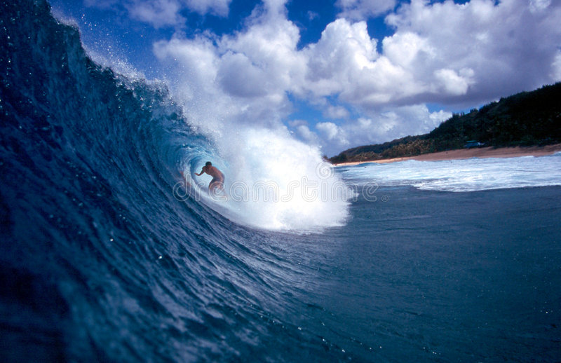 Surfer Surfing the Tube of a Blue Wave. Stock Photo of a surfer riding the tube of a blue wave on the North Shore of Oahu, Hawaii royalty free stock photos