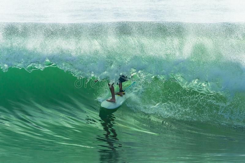 Surfer Surfing Tube Ride. Surfer surfing inside hollow ocean wave for a tube ride closeup photo action stock photo