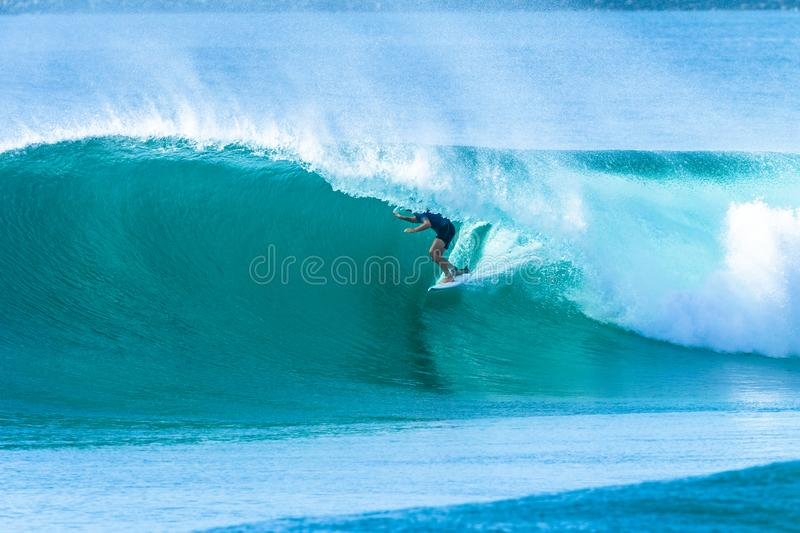 Surfer Surfing Tube Ride Hollow Wave. Surfer surfing tube rides hollow crashing blue ocean wave action photo royalty free stock photography