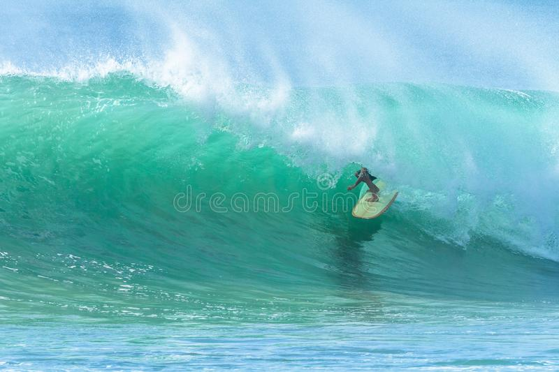 Surfer Surfing Tube Ride Hollow Wave. Surfer surfing tube rides hollow crashing blue ocean wave action photo royalty free stock photo