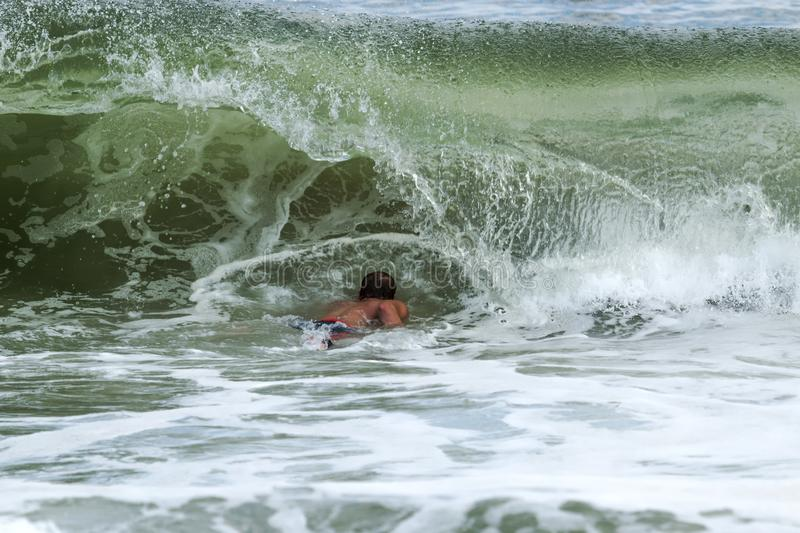 Surfer swimming under a wave as it curls over him royalty free stock image