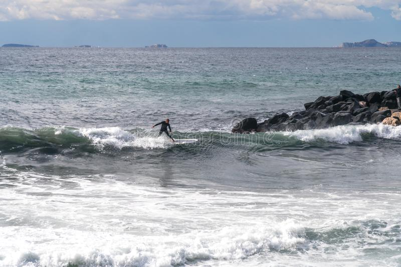 The surfer takes a wave, on a surfboard, slides along the wave, in the background of the mountain, Sorrento Italy stock image