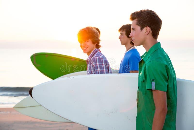 Surfer teen boys walking at beach shore royalty free stock photo