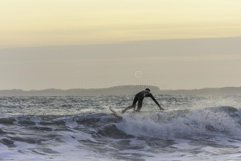 Surfer touching the wave while catching balance during evening surf in rough sea royalty free stock images