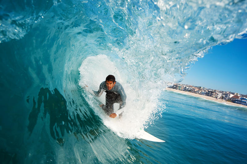 Surfer in the Tube. Surfer rides Big Wave, In the Tube with Blue Sky stock images