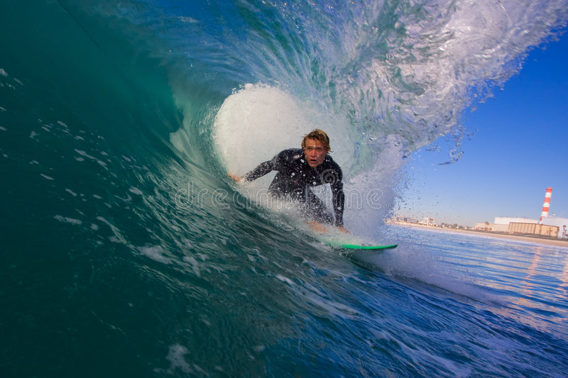 Surfer In The Tube. Surfer Gets an Epic Barrel On Big Wave with Beach in Background royalty free stock photography