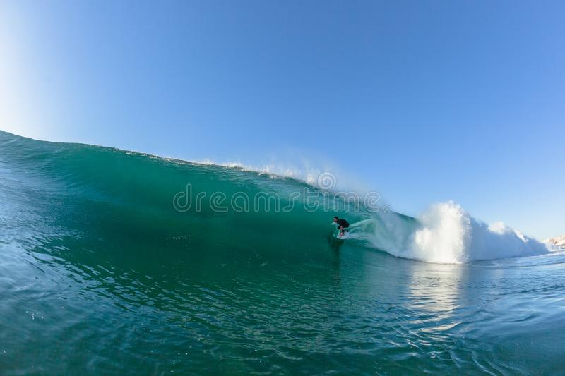 Surfing Surfer Tube Rides Wave Water Action. Surfing surfer Micheal Dunfy tube rides hollow ocean wave closeup swimming action photo stock photo