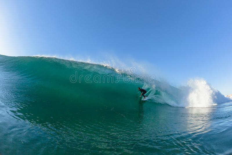 Surfing Surfer Tube Rides Wave Water Action. Surfing surfer Micheal Dunfy tube rides hollow ocean wave closeup swimming action photo royalty free stock photo