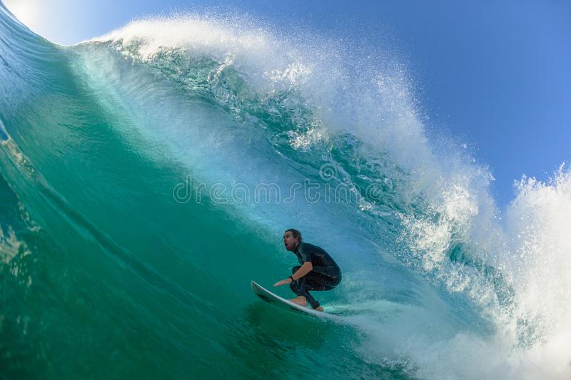 Surfing Surfer Tube Rides Wave Water Action. Surfing surfer Michael Dunphy tube rides hollow ocean wave closeup swimming action photo royalty free stock images