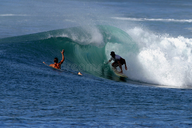 Surfer in the Tube of a Wave. A surfer rides a tubing wave while his friend looks on during a surf session on the north shore of Oahu, Hawaii royalty free stock image